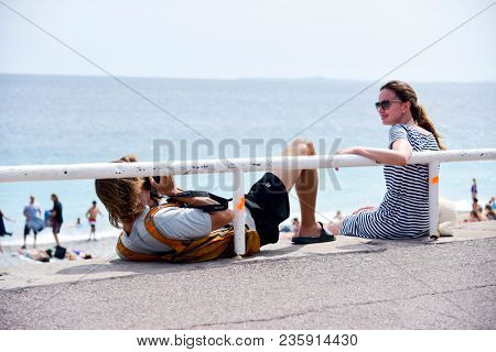NICE, FRANCE - JUNE 4, 2017: A young tourist man takes a picture of his partner at the famous Promenade des Anglais bordering the Mediterranean sea in Nice, in the French Riviera, France