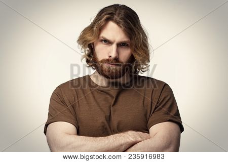 Tough Masculine Bearded Guy Standing With Crossed Arms Isolated On Grey Background. Serious Young Ma