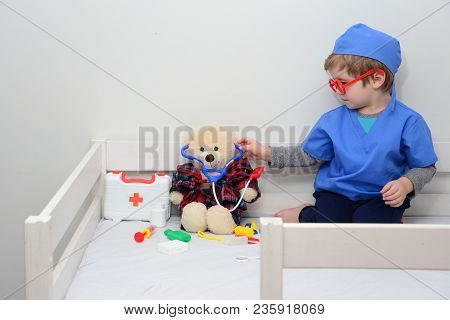 Baby Doctor, Boy Plays In Doctor, Toy Bear And Stethoscope. Cute Stuffed Teddy Bear Using Stethoscop