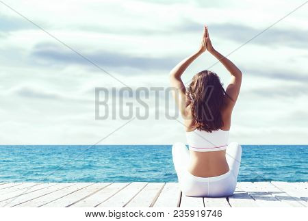 Attractive Woman In White Sporty Clothes Doing Yoga On A Wooden Pier. Yoga, Sport, Leisure, Recreati