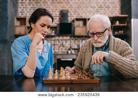 Old Man And Female Caregiver Playing Chess