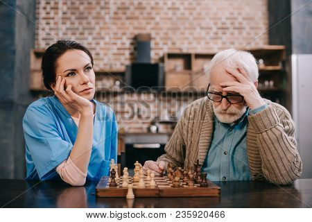 Bored Nurse And Elder Man Playing Chess