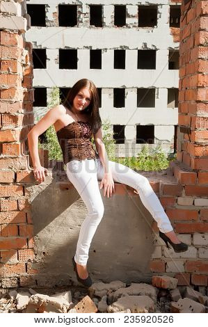 Beautiful Brunette Girl Against Background Of Ruins