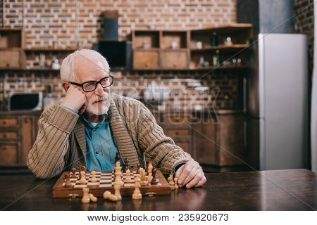 View Of Bored Senior Man Playing Chess