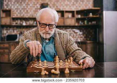 View Of Clever Senior Man Playing Chess Alone