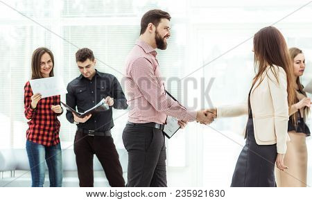 Handshake Manager And The Client In The Lobby Of A Modern Office