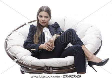 young business woman relaxes in a round chair