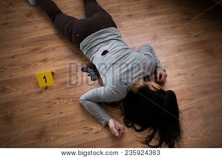 murder, kill and people concept - dead woman body in blood lying on floor and bullet sleeves at crime scene (staged photo)