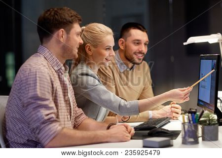 business, deadline and technology concept - coworkers working with graphics editor on computer screen late at night office