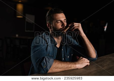 visitor sitting at bar counter and sniffing cigar poster