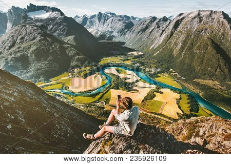 Man Taking Photo By Smartphone Sitting On Cliff Relaxing With Aerial Mountains Landscape Travel Acti