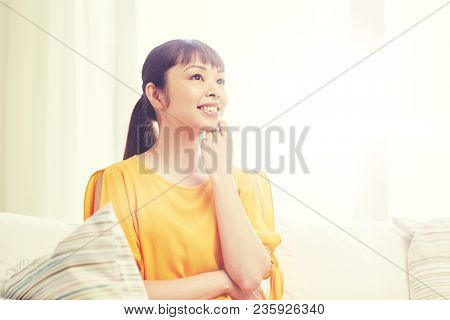 people, race, ethnicity and portrait concept - happy asian young dreaming woman at home