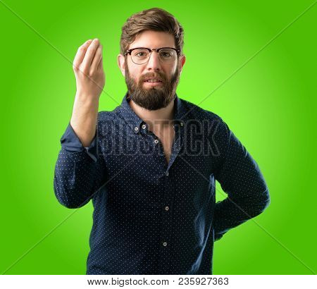 Young hipster man with big beard angry gesturing typical italian gesture with hand, looking to camera over green background