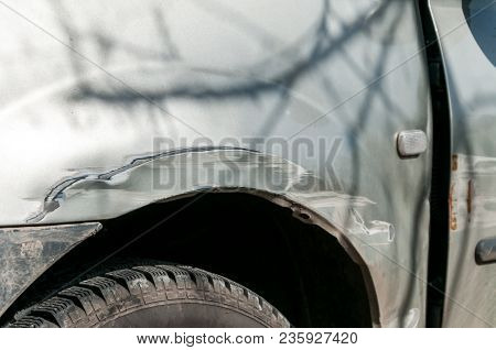 Damaged Car. Silver Damaged Car With Dented Aluminum Metal Body Scratched And Peeling Paint