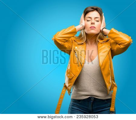 Beautiful young woman covering ears ignoring annoying loud noise, plugs ears to avoid hearing sound. Noisy music is a problem., blue background