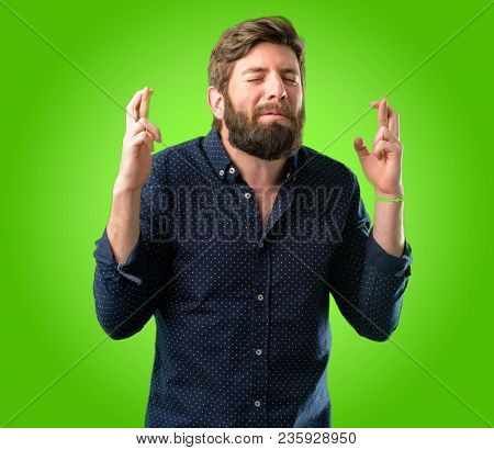 Young hipster man with big beard with crossed fingers asking for good luck over green background