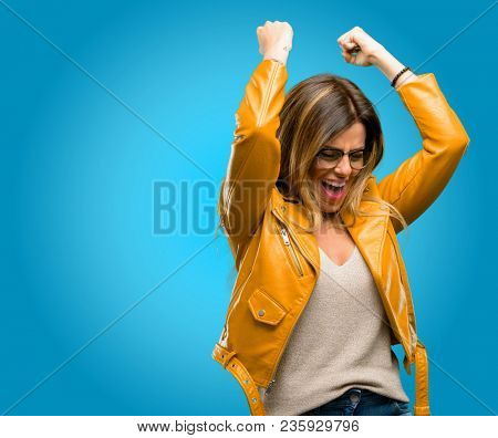 Beautiful young woman happy and excited expressing winning gesture. Successful and celebrating victory, triumphant, blue background