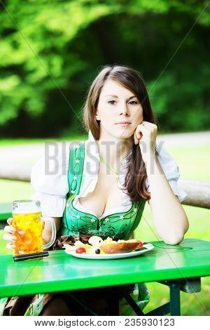Young Bavarian Woman In Dirndl Sitting At Table In Beer Garden With Beer And Food