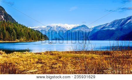 Fishing Boat Heading Up Pitt Lake With The Snow Capped Peaks Of The Golden Ears, Tingle Peak And Oth