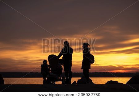 Father And Mother With A Baby In A Stroller And Children Silhouetted Against A Colorful Orange Sunse