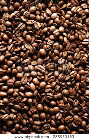Roasted coffee beans backgound, copy space, top view. Cappuccino, dark espresso, aroma black caffeine drink, ingredient for coffee beverage poster