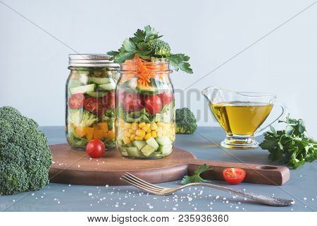 Vegetable Healthy Homemade Detox Colorful Salad In Mason Jar With Tomato, Lettuce, Broccoli On Blue
