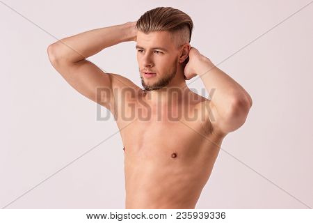 Portrait of shirtless young man posing to camera and looking away while isolated on white background. Handsome bearded hipster man showing his biceps. Muscular male model. Men's beauty and masculinity