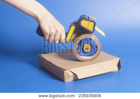 Woman Holding An Industrial Tape Dispenser, Cardboard Box Sealing On Blue