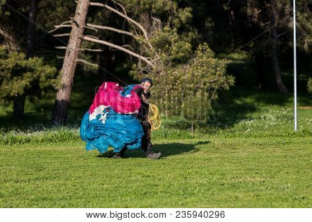 Man With A Paraglider On A Green Field After Landing Waving
