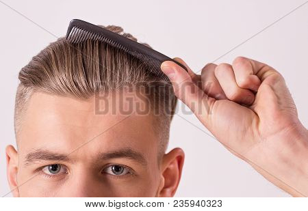 Close up of young attractive man brushing hair with comb in hand, isolated on white background. Man's face with modern and stylish haircut. Male beauty, hair style. Hipster combing hair or making hair