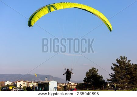 Drama, Greece -  April 8, 2018: Paragliders Fly Against Blue Sky In The Popular Area For Parachuting