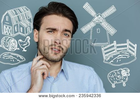 Thoughtful Farmer. Young Serious Farmer Standing With His Hand Touching His Neck And Thinking About