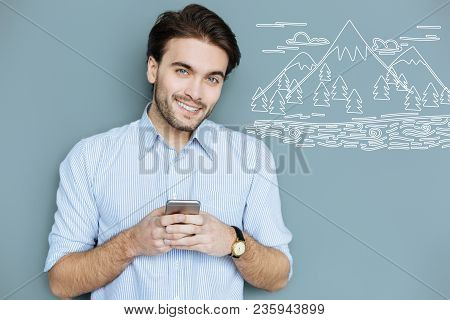 Pleasant Thoughts. Cheerful Handsome Employer Smiling While Standing With A Modern Smartphone And Th