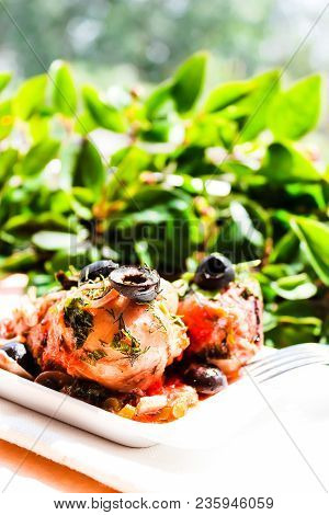 Mediterranean Style Fried Chicken In Tomato Sauce With Celery, Black Olives And Parsley On A White P