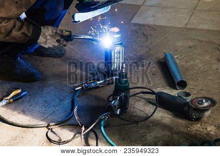 Repairing Of Corrugation Muffler Of Exhaust System In Car Workshop - Welder Welds The Pipe On Corrug