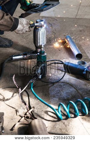 Repairing Of Corrugation Muffler Of Exhaust System In Car Workshop - Welder Fixes The Pipe On Corrug