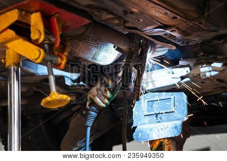 Repairing Of Corrugation Muffler Of Exhaust System In Car Workshop - Welder Welds The Silencer On Ex
