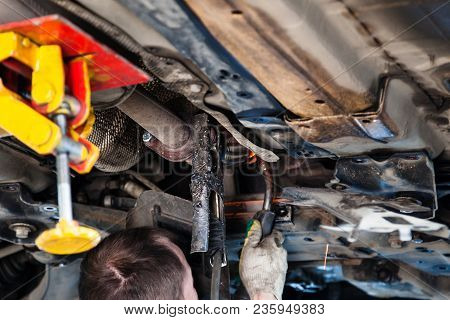 Repairing Of Corrugation Muffler Of Exhaust System In Car Workshop - Repairer Welds The Silencer On