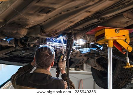 Repairing Of Corrugation Muffler Of Exhaust System In Car Workshop - Serviceman Welds The Silencer O