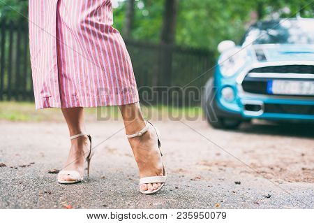 Tidy Tanned Sexual Soft Woman Feet In High-heeled Peep-toes With Modern Car On Background. Summertim