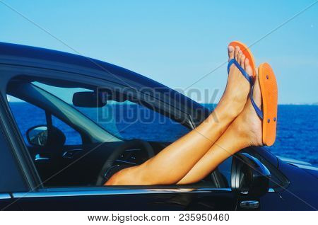closeup of a young caucasian man, wearing a pair of orange flip-flops, relaxing in a car next to the oceans