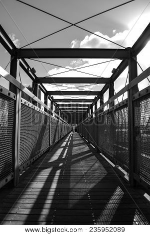 A Black And White Symmetrical Walkway With Shadows