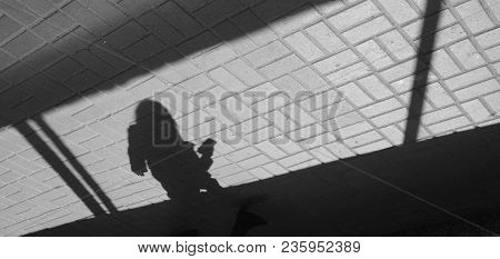 Silhouette Person, Girl With Mobile Telephone  In Underground Passage. Shadow And Light On Paving Sl
