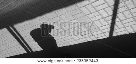 Silhouette Person Bow-backed, Hunched Crooked Man In Underground Passage. Shadow And Light On Paving
