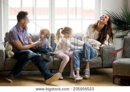 Happy Parents And Kids Having Fun Tickling Sitting Together On Sofa, Cheerful Couple Laughing Playin