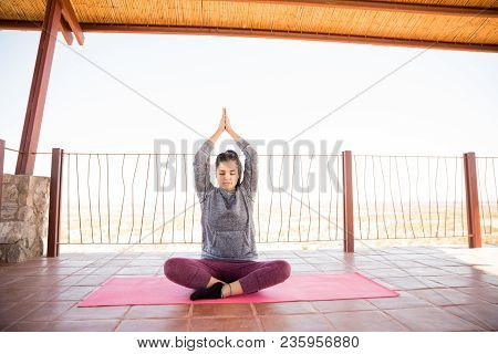 Portrait Of Beautiful Hispanic Woman Relaxing In A Easy Yoga Pose And Meditating At Fitness Studio
