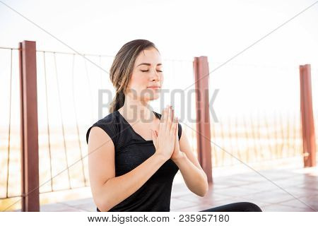Portrait Of Beautiful Young Woman Sitting In Yoga Meditation Pose With Her Eyes Closed And Hands Joi