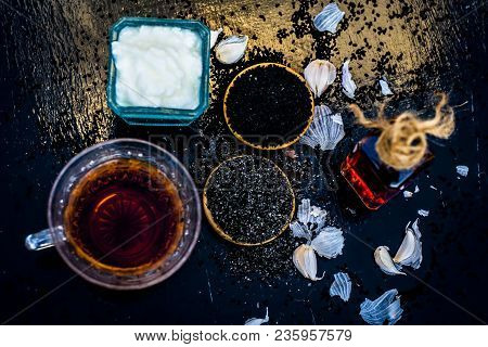 Close Up Of Kalonji With Curd Or Youghurt On Wooden Surface With Black Tea And Its Extracted Oil And