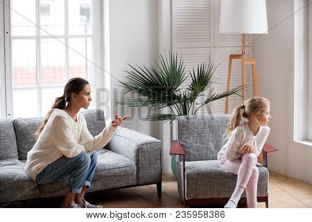 Young Strict Mother Or Sister Scolding Stubborn Sulky Kid Girl In Living Room At Home, Offended Daug