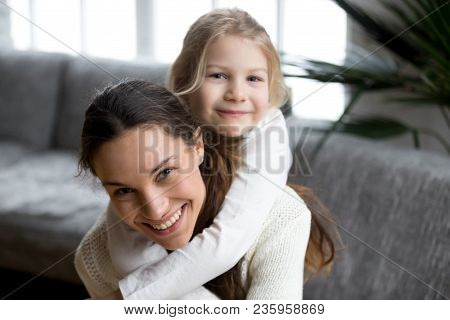 Happy Single Mother Laughing Piggybacking Little Girl At Home, Smiling Mom And Daughter Having Fun P